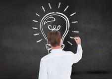 Man drawing a light bulb on blackboard Royalty Free Stock Image