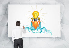 Man drawing light bulb in office Royalty Free Stock Photography