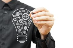 Man drawing light bulb with sprockets. Vision,idea, and innovati Royalty Free Stock Photos