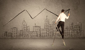 Man drawing line above the city. A man in elegant suit standing on a small ladder and drawing a line on brown wall background with buildings Stock Photos