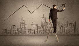 Man drawing line above the city. A man in elegant suit standing on a small ladder and drawing a line on brown wall background with buildings Royalty Free Stock Image