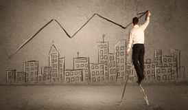 Man drawing line above the city. A man in elegant suit standing on a small ladder and drawing a line on brown wall background with buildings Stock Image