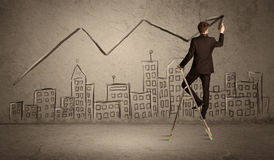 Man drawing line above the city. A man in elegant suit standing on a small ladder and drawing a line on brown wall background with buildings Royalty Free Stock Photography