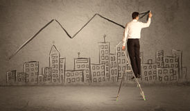 Man drawing line above the city. A man in elegant suit standing on a small ladder and drawing a line on brown wall background with buildings Stock Photo