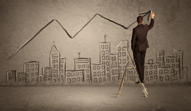 Man drawing line above the city. A man in elegant suit standing on a small ladder and drawing a line on brown wall background with buildings Stock Photography