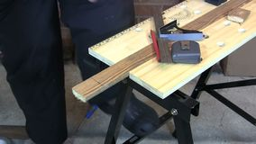 Man drawing a line and cutting a piece of wood with a saw stock video