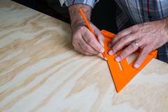 Man drawing line with 45 degree triangle on wood Stock Images
