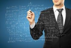 Man drawing mathematical formulas. Businessman drawing mathematical formulas on a blue background Stock Image