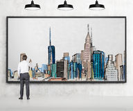 Man drawing New York. Young businessman drawing a picture of New York city centre with colours in a frame, three lamps above. Back view. Concept of dreaming Stock Image