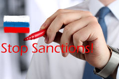 Man drawing a phrase stop  sanctions  by a  red pen . Royalty Free Stock Images