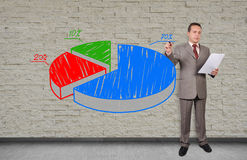 Man drawing pie chart. Businessman drawing pie chart on an invisible wall Royalty Free Stock Image