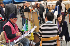 Man drawing a portrait of an asian  couple. Piazza Navona. Rome. Italy Stock Photography
