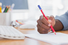 Man drawing with a red pencil on a desk Royalty Free Stock Photo