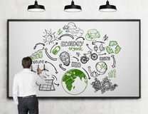 Man drawing renewable energy sources sketches at whiteboard Royalty Free Stock Photo