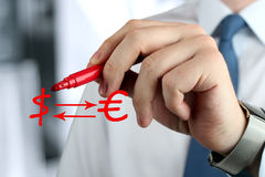 Man drawing a sign of  euro with question by red pen. The Man drawing a sign of  euro with usd  by red pen Royalty Free Stock Photos
