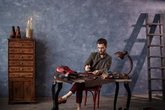 Man drawing the sole of shoe. Boots and shoes manufacturing concept royalty free stock photos