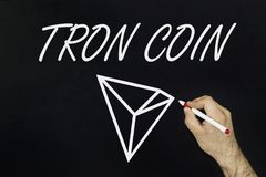 Man drawing a symbol of new cryptocurrency - Tron Coin on blackboard. Man drawing a symbol of new cryptocurrency - Tron Coin on the blackboard Stock Photos