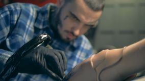 A man drawing a tattoo on an artificial arm, bionic prosthesis. 4K stock video footage