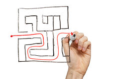 Man drawing the way out through a maze. On a whiteboard royalty free stock images