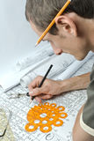 Man and drawings. Drawing and various tools close-up Stock Images