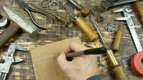 Man draws a draft. Indicates dimensions. Vintage tools on background stock footage