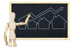 Man draws a graph of real estate sales growth on a blackboard. Abstract image with wooden puppet Royalty Free Stock Photo