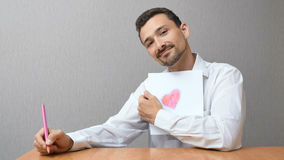 A man draws a heart shape. A man in a white shirt is holding a drawing. a person draws a heart shape Royalty Free Stock Photo