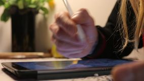 Man draws a pen on the screen. On the table, close-up stock video footage