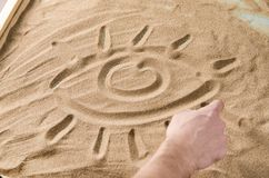 A man draws on the sand symbol of eye Royalty Free Stock Image