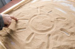 A man draws on the sand symbol of the sun Royalty Free Stock Images