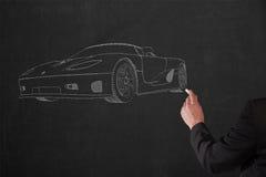 Man draws a sportscar on a black chalkboard by hand Royalty Free Stock Photo