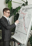 Man draws trading diagramms on the papper presentation board royalty free stock photography