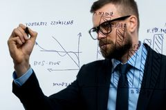 Man draws various growth charts, calculating prospects for success in a modern glass office. Businessman draws various growth charts, calculating prospects for stock photo