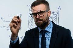 Man draws various growth charts, calculating prospects for succe. Businessman draws various growth charts, calculating prospects for success in a modern glass Stock Photo