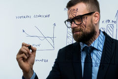 Man draws various growth charts, calculating prospects for succe. Businessman draws various growth charts, calculating prospects for success in a modern glass Stock Image