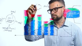 Man draws various growth charts, calculating prospects for success in a modern glass office stock video