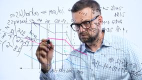 Man draws various growth charts, calculating prospects for success in a modern glass office stock video footage