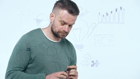 Man draws various growth charts, calculating prospects for success in a modern glass office. Businessman draws various growth charts, calculating prospects for stock footage
