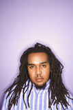Man with dreadlocks. Serious African-American mid-adult man on purple background with dreadlocks Royalty Free Stock Photo