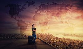 Man dreamer standing with suitcase on the rooftop of a skyscraper planning his next holiday destination royalty free stock photography