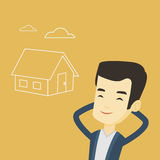 Man dreaming about buying new house. Asian man dreaming about future life in a new house. Smiling man planning future purchase of his own house. Young man Royalty Free Stock Images