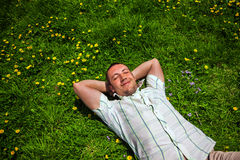 Man dreaming lying on the grass. Man dreaming lying smiling on the grass Royalty Free Stock Photo