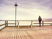 Man dreaming sitting on a wooden pier near the water stock image