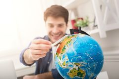Man dreaming about travel, looking at globe. Young cheerful man dreaming about air travel around world, looking at globe at home. Handsome guy playing with toy Royalty Free Stock Image