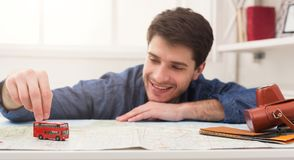 Man dreaming about travel, looking at map. Young cheerful man dreaming about bus travel around world, playing with toy bus on map and choosing route of vacation Royalty Free Stock Images