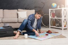 Man dreaming about travel, looking at map. Young serious man dreaming about bus travel around world, looking at toy bus on map and choosing route of vacation Stock Photography