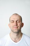 Man in dreams. Portrait of positive bald-headed man with closed eyes on white background Royalty Free Stock Photos