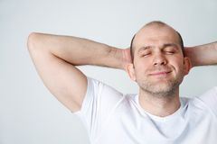Man in dreams. Portrait of positive bald-headed smiling man on white background Royalty Free Stock Images