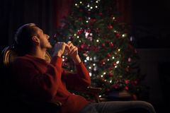 The man dreams sitting by the Christmas tree Stock Photo