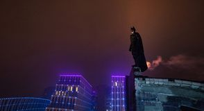 A man dressed as a bat stands against the background of night city lights and sky royalty free stock photography